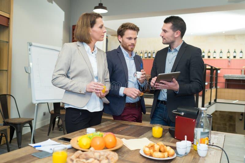 Employees having breakfast meeting. Employees having a breakfast meeting royalty free stock image