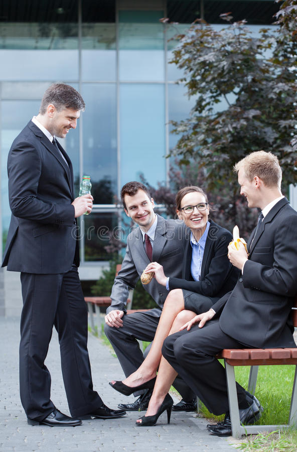 Employees having lunch outdoors stock image