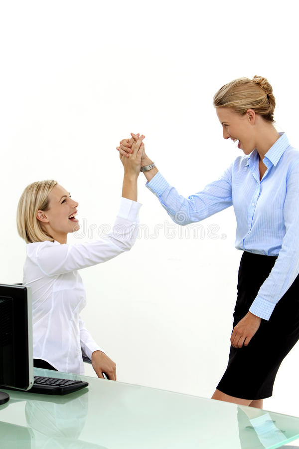 Employees High five at workplace. Two young blond hair women only. Isolated on white royalty free stock photography