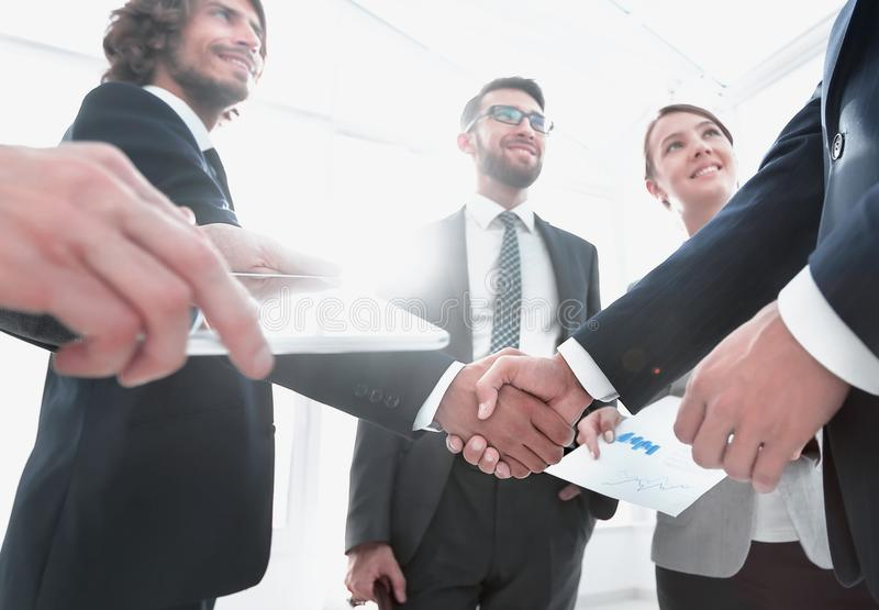 Employees look at the handshake business partners. The concept of teamwork stock image