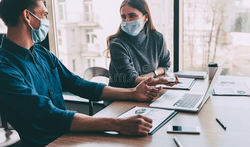 Employees in protective masks work in the office. royalty free stock images