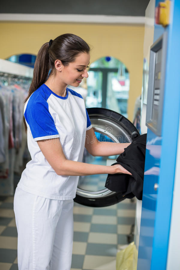 Employees putting clothes in the dryer royalty free stock image