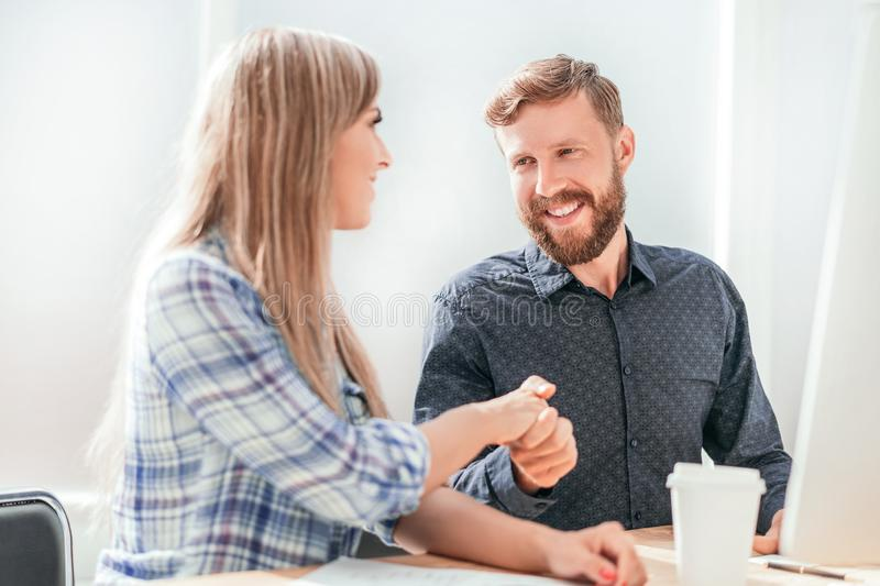 Employees shaking hands sitting at the Desk. stock photography