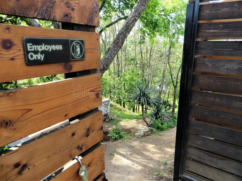 Employees Only sign on gate. Behind trendy restaurant, wooden gate marked Employees Only opens to gravel path and woods leading downhill toward river, Austin royalty free stock photography