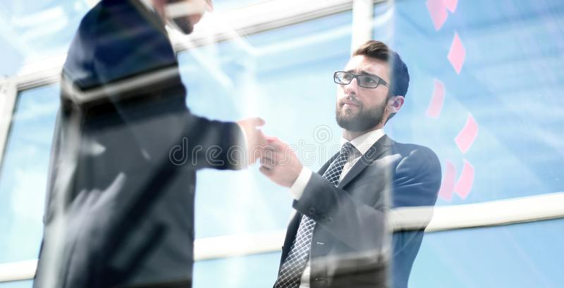 Employees standing near a transparent office wall. royalty free stock image