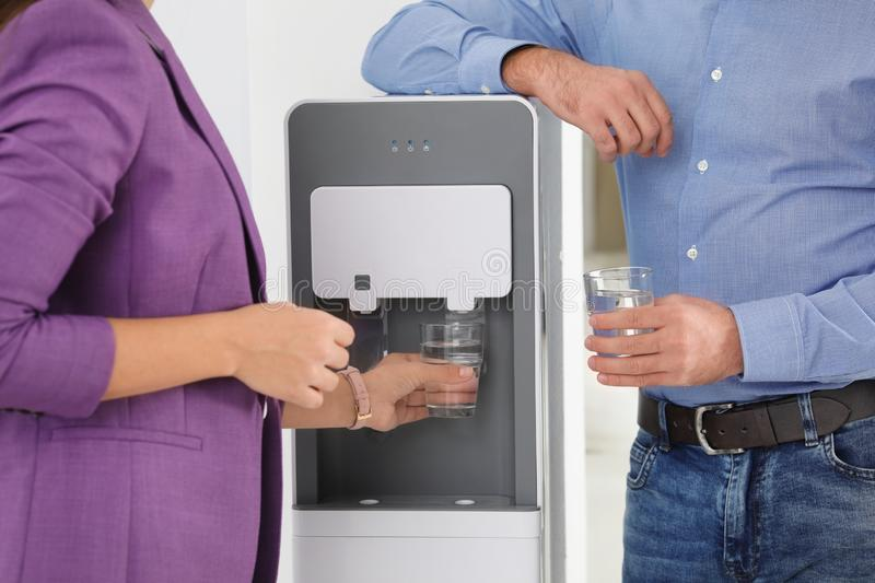 Employees taking glasses of water from cooler in office. Closeup stock photo
