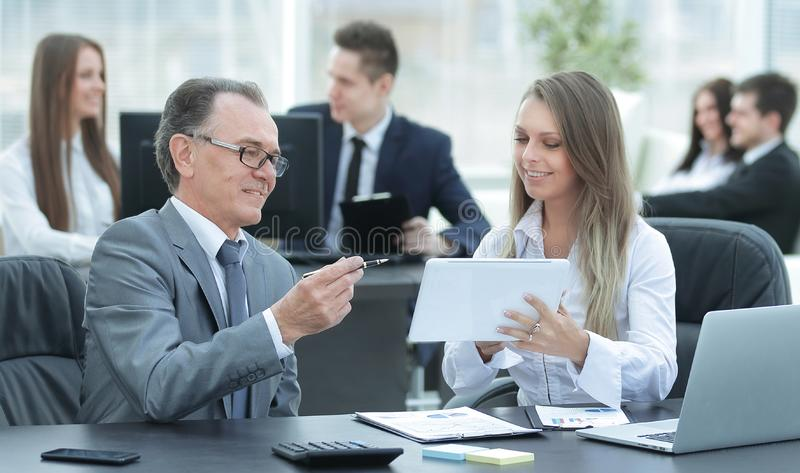 Employees using digital tablet to work with financial data stock image
