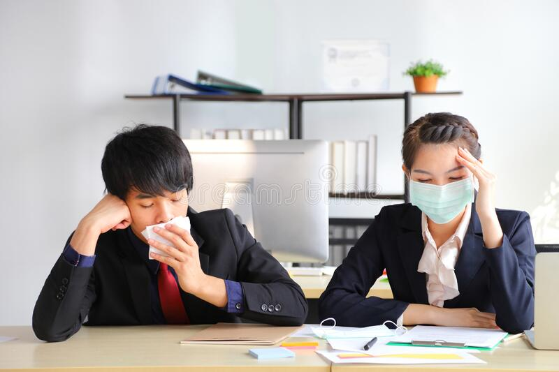 Employees working in business office got fever and cold while wearing medical face mask for protecting and preventing virus. Employees working in business office stock photography