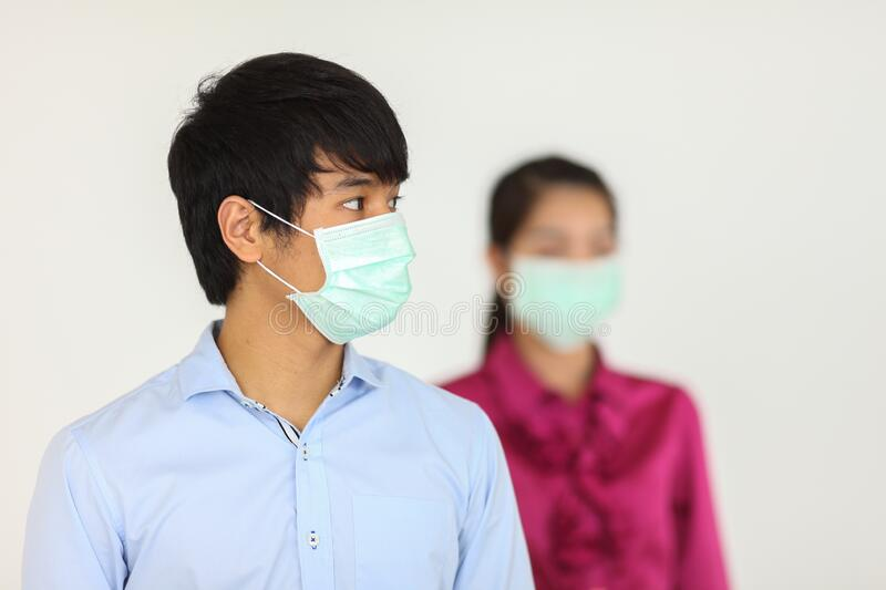 Employees working in business office while wearing medical face mask. On white background stock image