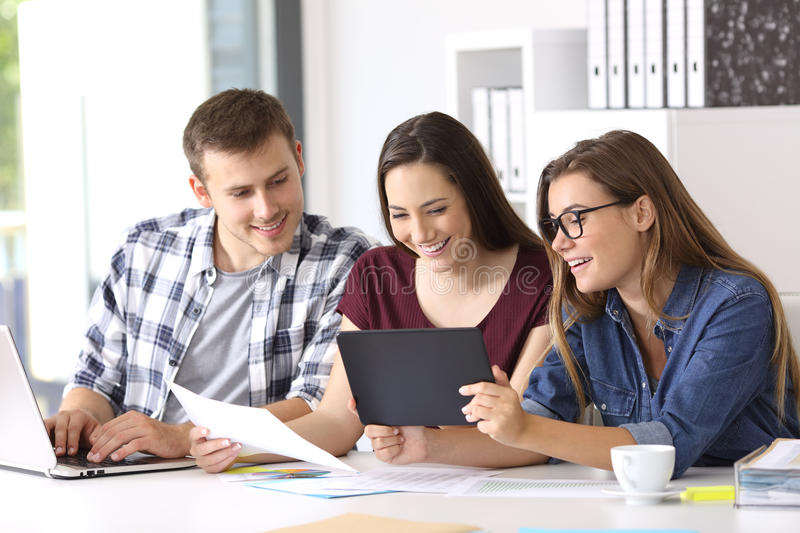 Employees working on line with tablet at office. Three happy employees working on line with a tablet and documents at office royalty free stock photography