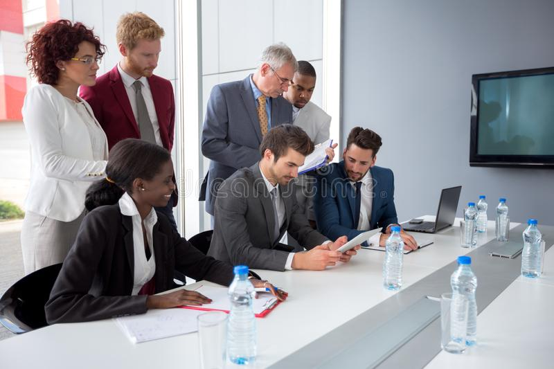 Employer follow data from tablet in company meeting stock images