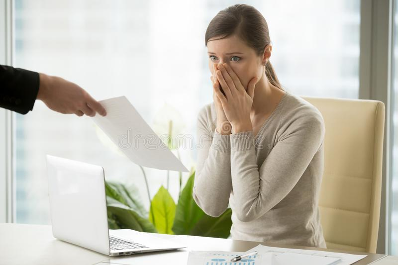 Employer giving dismissal notice to young woman. Young women shocked when receiving dismissal notification from boss. Upset female employee worrying because of royalty free stock photography