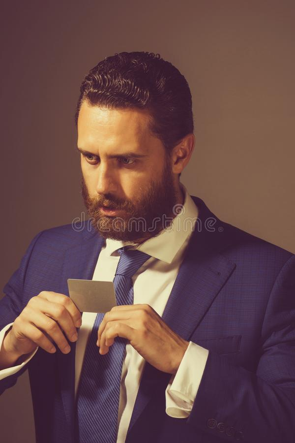 Employer or man showing business or credit card, business ethics. Employer or man showing business or credit card in blue formal outfit on grey background, copy royalty free stock images