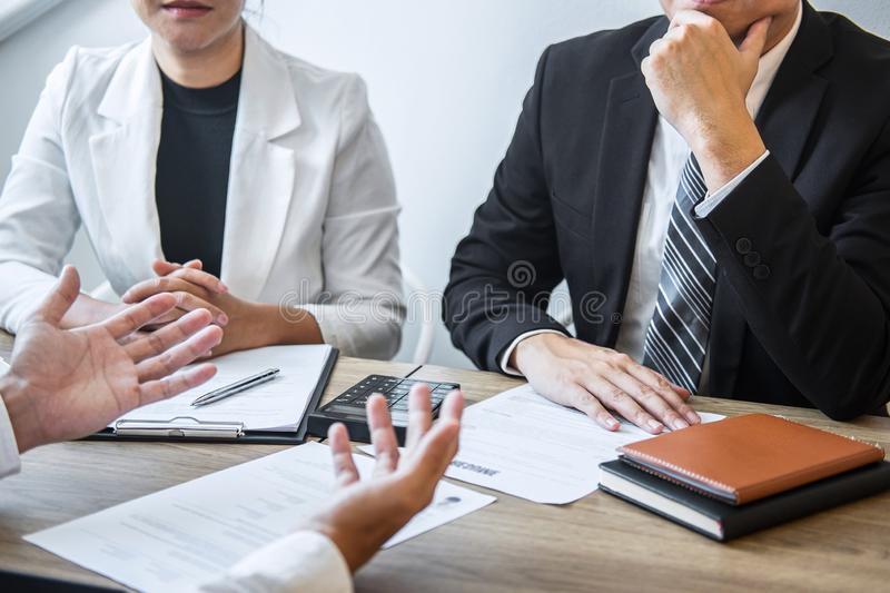 Employer or recruiter holding reading a resume with talking during about his profile of candidate, employer in suit is conducting stock image