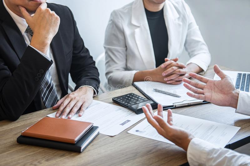 Employer or recruiter holding reading a resume with talking during about his profile of candidate, employer in suit is conducting royalty free stock photos