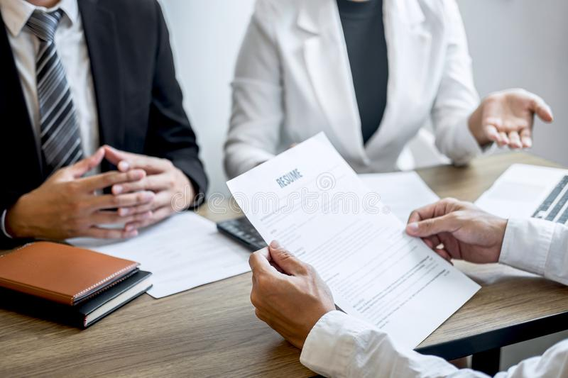 Employer or recruiter holding reading a resume with talking during about his profile of candidate, employer in suit is conducting stock photography