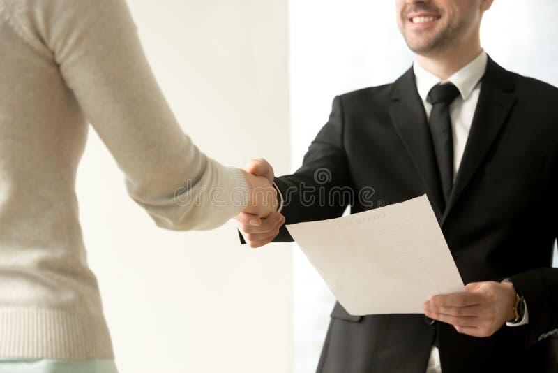 Employment handshake closeup, employer shaking new hire hand, of. Employment handshake, smiling friendly employer shaking new hire hand, happy businessman stock photography