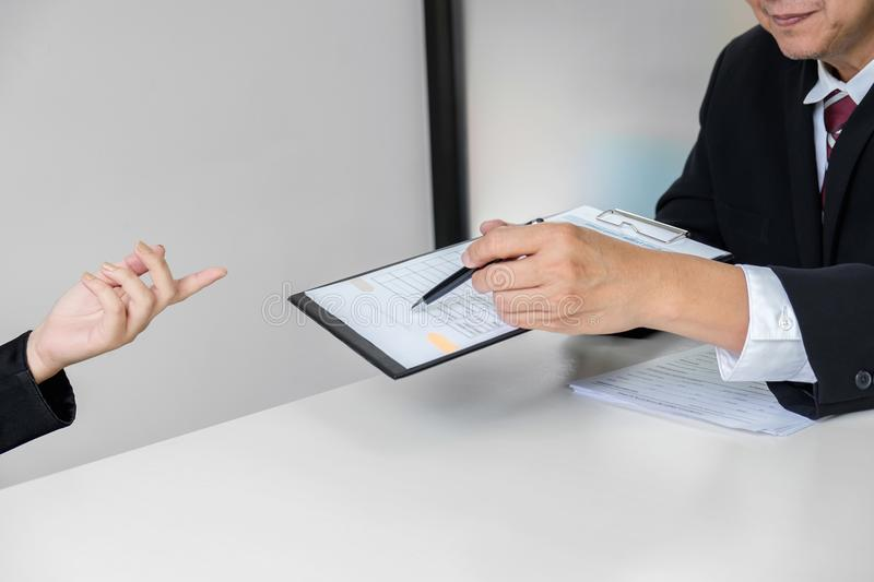 Employment and recruitment concept, Board reading a resume during a job interview and candidate sign contract for new colleagues stock image