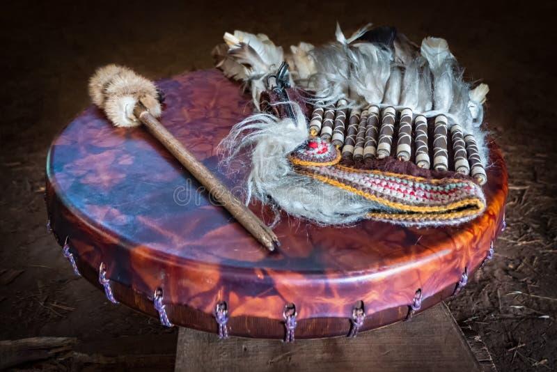 Emplume-se a mantilha, o pandeiro antigo do couro do amerindian e o pilão do cilindro Atributos do indiano americano antigo fotografia de stock