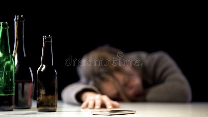 Empoisonnement d'alcool de souffrance femelle dormant près du téléphone sur la table, soins médicaux photo libre de droits