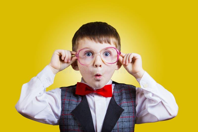 Empollón alegre sonriente feliz del niño pequeño con los vidrios en sus oídos i imágenes de archivo libres de regalías