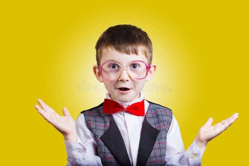 Empollón alegre sonriente feliz del niño pequeño con los vidrios en sus oídos i foto de archivo