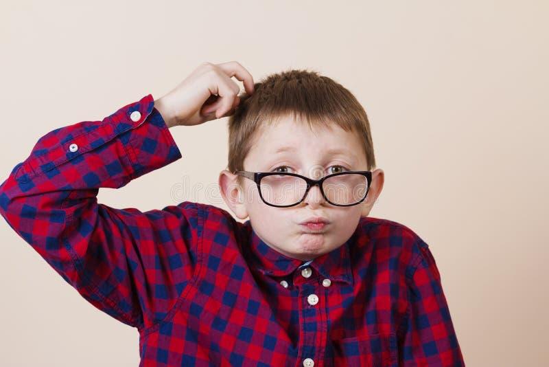 Empollón confuso del niño pequeño, llevando a cabo un cubo del rompecabezas y una mano en hola imagen de archivo libre de regalías