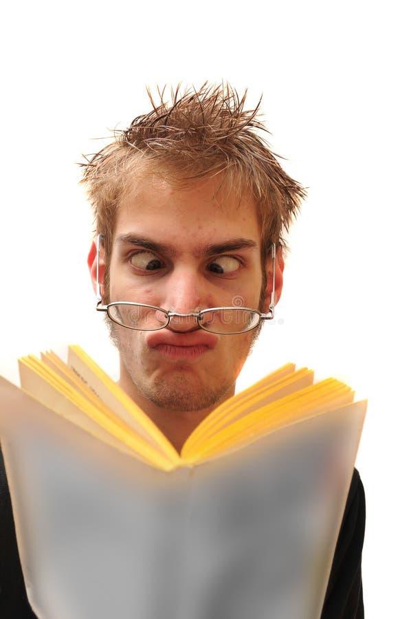 Empollón extraño que lee un libro imagen de archivo