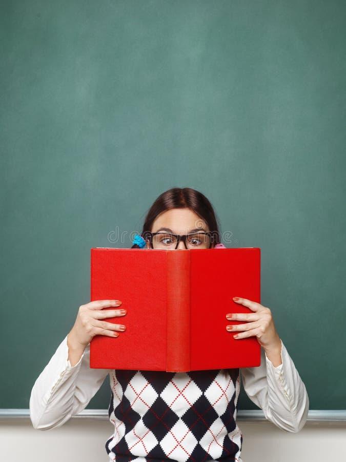 Empollón femenino joven que sostiene el libro fotografía de archivo