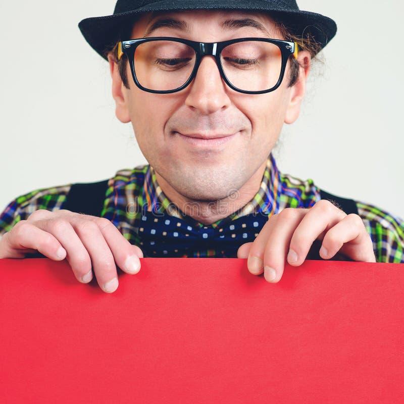 Empollón masculino divertido que mira abajo en el cartel rojo vacío Hombre feliz en los vidrios que sostienen la hoja de papel pa fotos de archivo