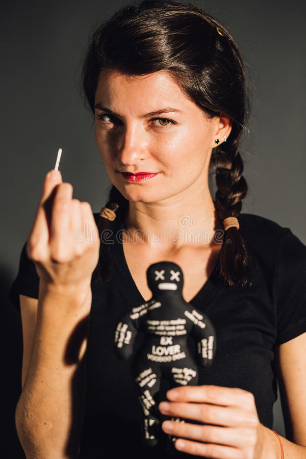 Empowered furious woman. Empowered furious young woman holding a voodoo doll and a needle royalty free stock photography
