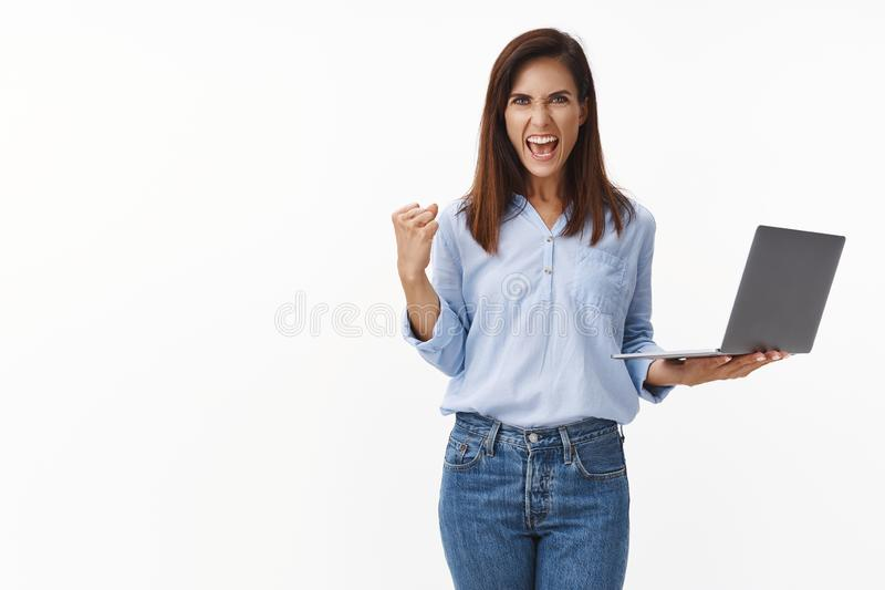 Empowered good-looking businesswoman feel success and joy, hold laptop, fist pump celebrating good deal, shout yeah yes royalty free stock images