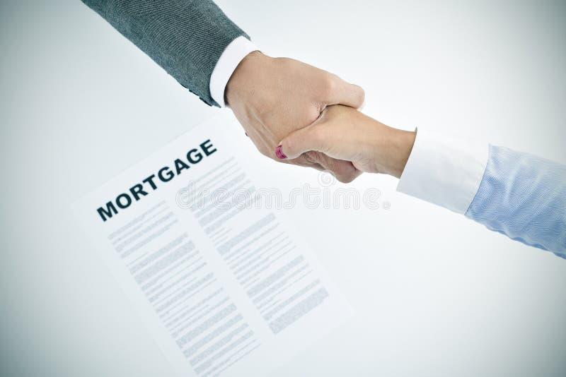 Empréstimo hipotecário e homem e mulher que agitam as mãos, vignetted fotos de stock