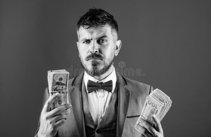 Empréstimos de dinheiro fáceis Pilha formal da posse do terno do homem do fundo azul das cédulas do dólar O homem de negócios obt imagens de stock royalty free