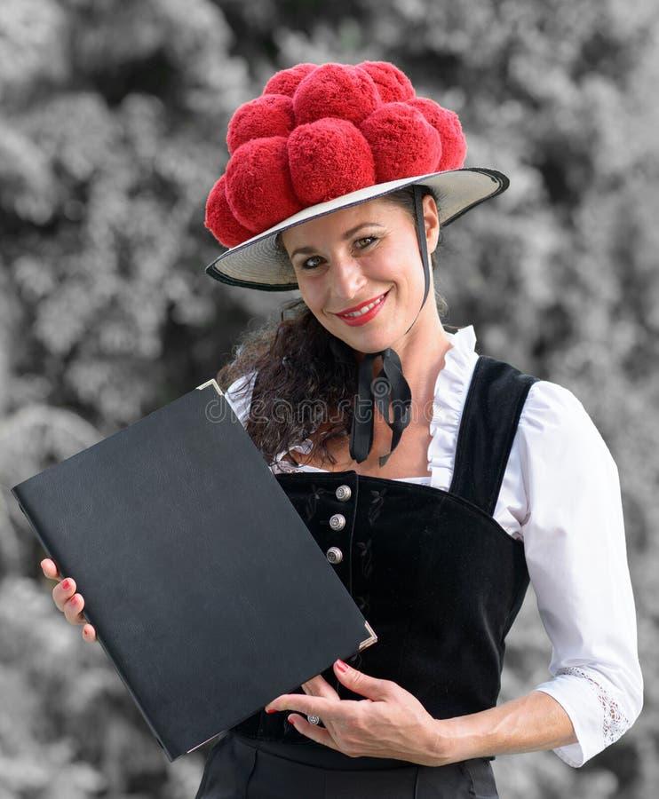Empregada de mesa alemão que guarda um menu que veste um bollenhut fotos de stock royalty free