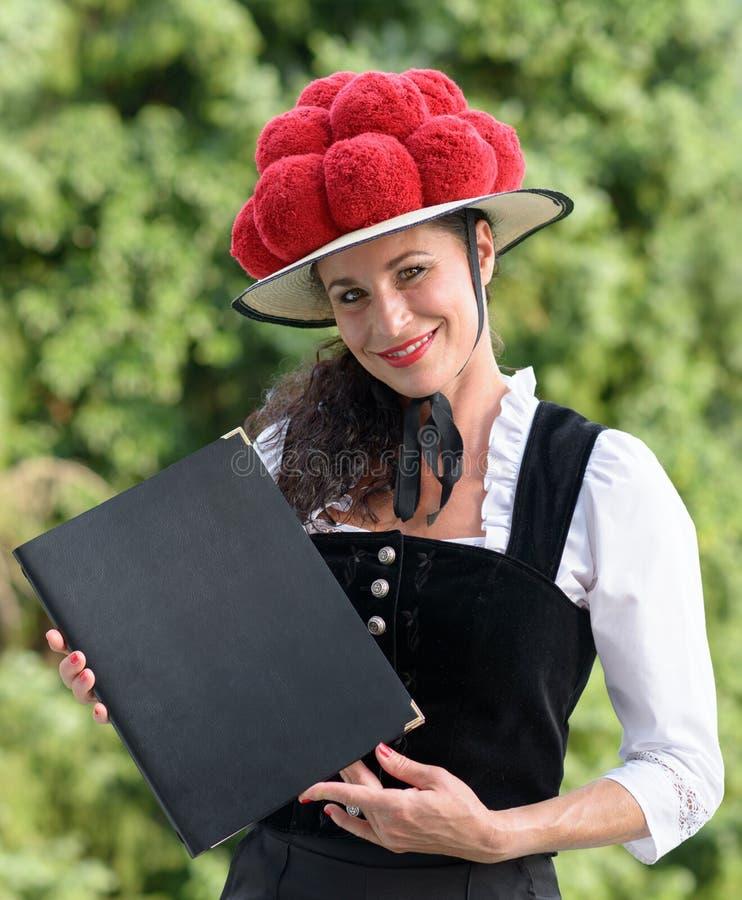 Empregada de mesa alemão que guarda um menu que veste um bollenhut foto de stock royalty free