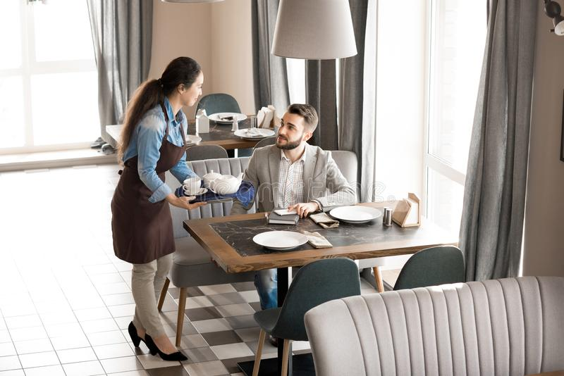 Empregada de mesa amigável que dá o chá ao cliente foto de stock royalty free