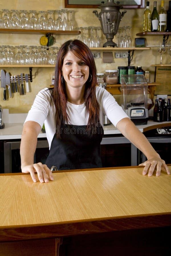 Empregada de mesa atrás do contador que trabalha no restaurante imagem de stock royalty free