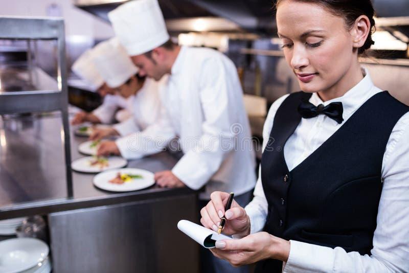Empregada de mesa com a almofada de nota na cozinha comercial fotos de stock royalty free