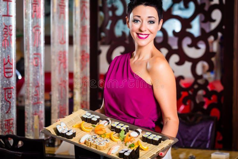 Empregada de mesa com o sushi no restaurante fotografia de stock