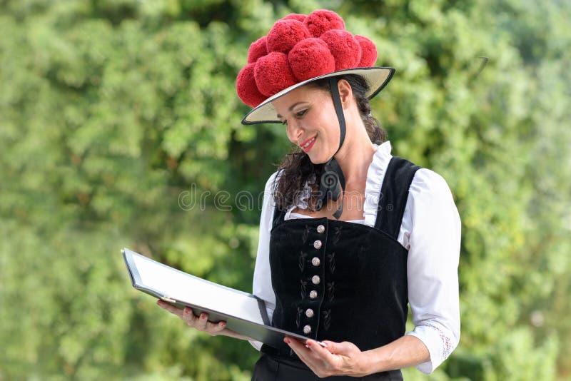Empregada de mesa consideravelmente alemão no bollenhut que lê um menu fotografia de stock royalty free