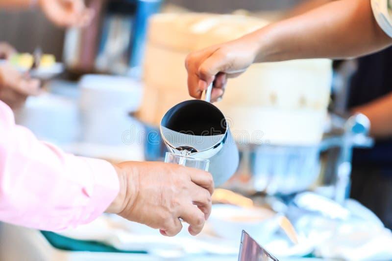 A empregada de mesa da mão derrama a água na sala fotografia de stock royalty free