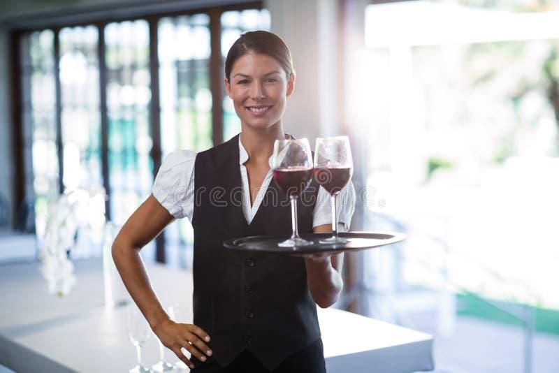 Empregada de mesa de sorriso que guarda uma bandeja com vidros do vinho tinto imagens de stock royalty free
