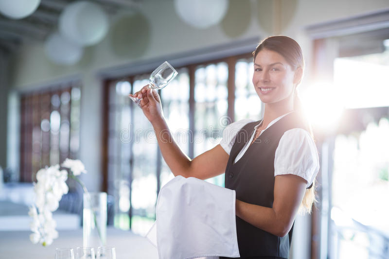 Empregada de mesa de sorriso que sustenta um vidro de vinho vazio imagens de stock royalty free