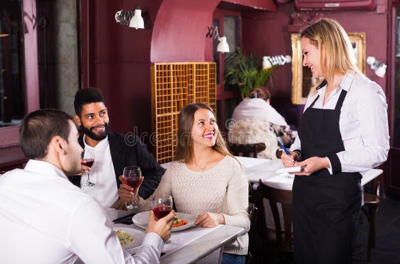 Empregada de mesa e convidados de sorriso na tabela imagem de stock