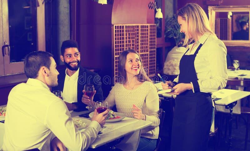 Empregada de mesa e convidados de sorriso na tabela foto de stock royalty free