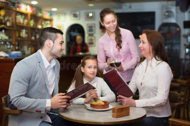 Empregada de mesa e família no café imagem de stock