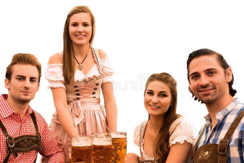 A empregada de mesa entrega cervejas na barraca com visitantes felizes em uma barraca da cerveja em Munich Oktoberfest imagens de stock