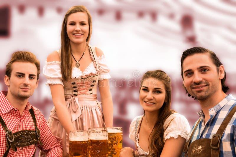A empregada de mesa entrega cervejas na barraca com visitantes felizes em uma barraca da cerveja em Munich Oktoberfest imagem de stock royalty free