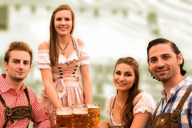 A empregada de mesa entrega cervejas na barraca com visitantes felizes em uma barraca da cerveja em Munich Oktoberfest foto de stock